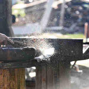 Mulheres, paneleiras de Goiabeiras, açoitando panelas com tanino extraido de mangue, durante processo de queima.