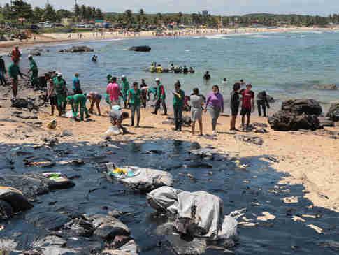 Equipes e voluntários trabalham para  conter manchas na praia Pedra de Xaréu,  no município do Cabo de Santo Agostinho, em Pernambuco