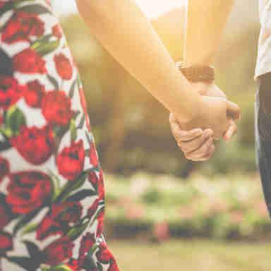 Casal de mãos dadas andado ao ar livre