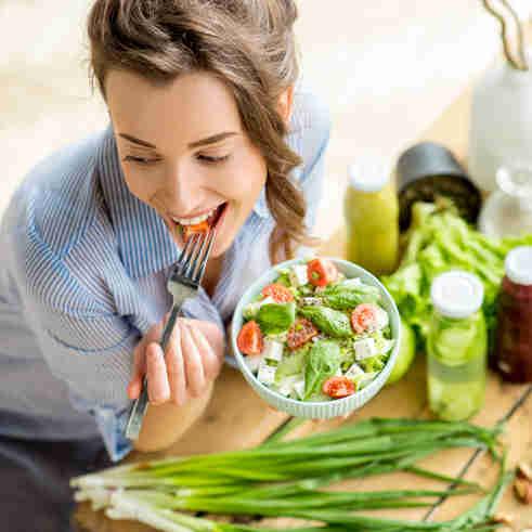 Mulher jovem e feliz comendo salada saudável, sentado à mesa com ingredientes frescos verdes dentro de casa