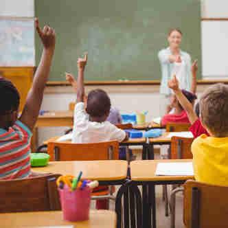 Crianças na sala de aula levantando o dedo para responder a pergunta da professora
