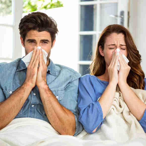 Jovem casal assoando o nariz em lenço em casa