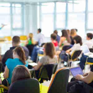Jovens ouvindo explicaçao de professor na sala de aula