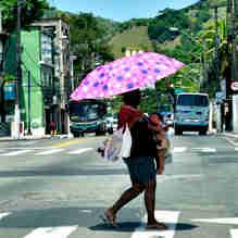 Data: 30/10/2019 - ES - Vitória - Mulher usa sombrinha para proteger criança do sol forte na Avenida Maruípe