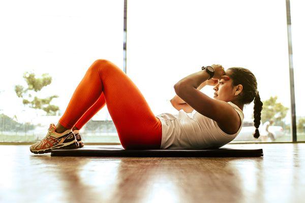 Mulher fazendo abdominal: exercício ajuda a perder barriga?