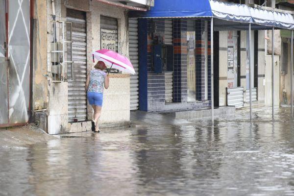 Mulher enfrentando ruas alagadas durante chuva: previsão é de mais temporais. Crédito: Carlos Alberto Silva/Arquivo