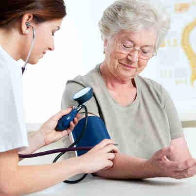Enfermeira medindo a pressão de mulher idosa