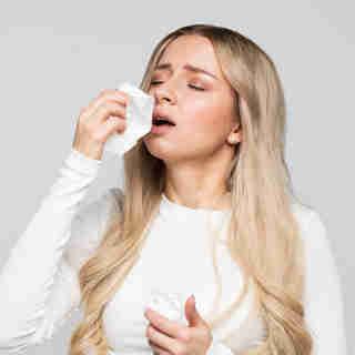 Mulher com resfriado segurando lenço