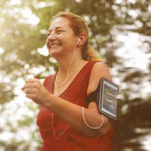 Mulher praticando exercícios físicos ouvindo música no celular