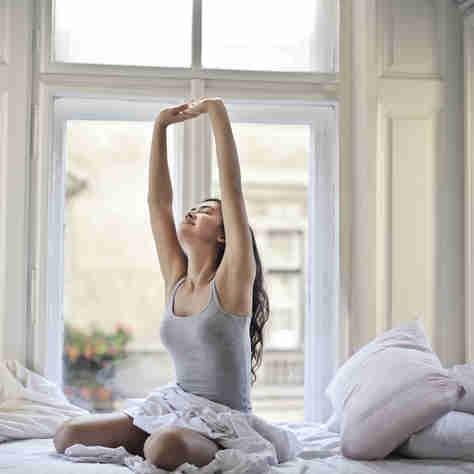 Mulher se espreguiçando: hábito traz vários benefícios à saúde