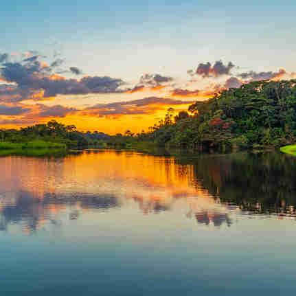 Reflexão de um pôr do sol junto a uma lagoa dentro da Bacia da Floresta Amazônica.