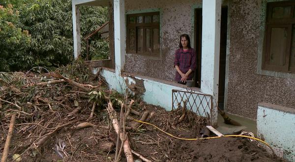 Moradora de Ubá observa quintal tomado pela lama. Crédito: Reprodução/ TV Gazeta Sul