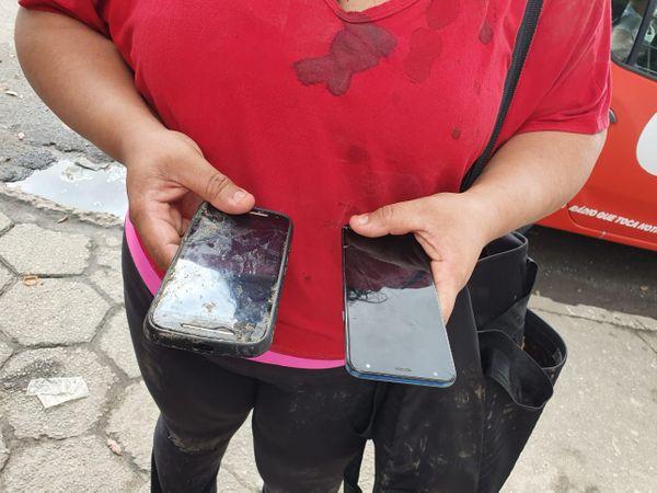 Mulher carrega dois celulares, um deles quebrado, para entregar a ladrão. Crédito: Isaac Ribeiro