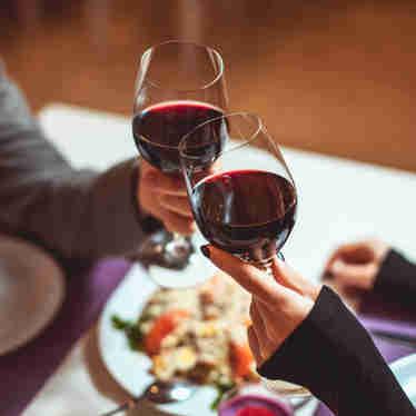 Casal brinca com taças de vinho em restaurante