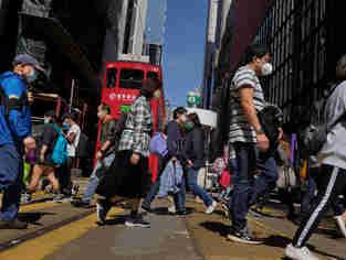 Pedestres usam máscaras de proteção nas ruas da cidade de Hong Kong, território chinês semiautônomo, nesta quarta-feira, 26. A China informou que foram registrados novos 406 casos e 52 mortes decorrentes de infecção pelo coronavírus