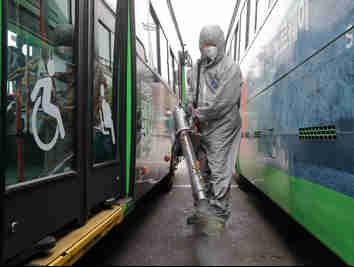 Trabalhadores vestindo roupas de proteção pulverizam desinfetante como precaução contra o coronavírus em uma garagem de ônibus em Seul, na Coreia   do Sul