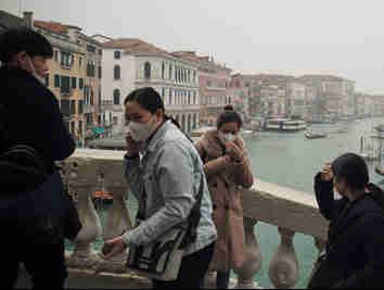 Turistas usam máscaras de proteção na cidade de Veneza, na Itália, onde o tradicional evento de carnaval foi cancelado devido ao surto do novo coronavírus