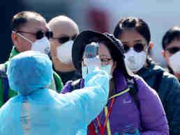 Um oficial mede a temperatura dos passageiros estrangeiros desembarcados do navio de cruzeiro Diamond Princess antes do embarque em um ônibus no  Porto de Yokohama, perto de Tóquio.