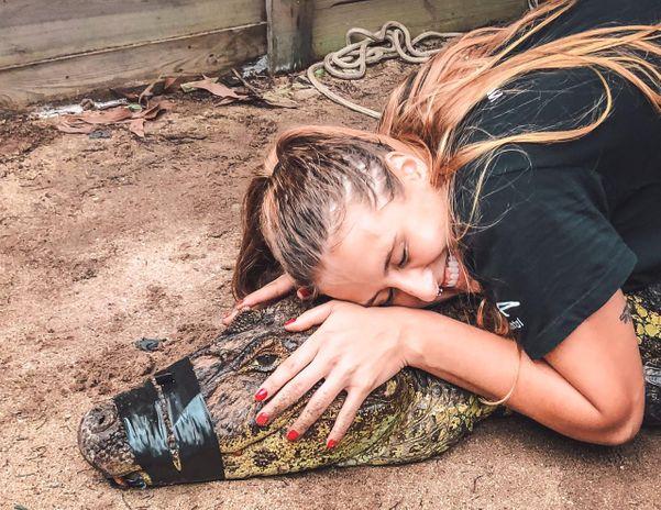 Estagiária Julie participou da captura e tirou a foto abraçadinha com o jacaré. Teria coragem?. Crédito: Divulgação | Projeto Caiman