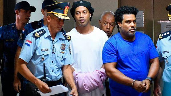 Ronaldinho Gaúcho e irmão chegam algemados para audiência sobre uso de passaportes falsos. Crédito: Agência Lance