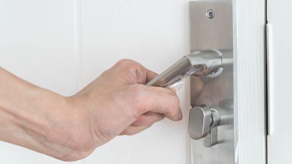Pessoa segurando maçaneta da porta