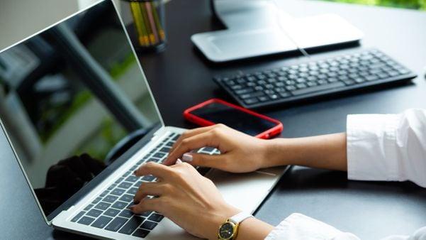 Mulher digitando no teclado do laptop na mesa, trabalhando com o dispositivo de tecnologia no escritório