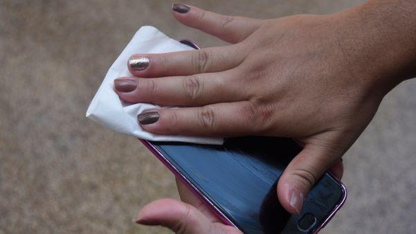 Pessoa limpando a tela do celular
