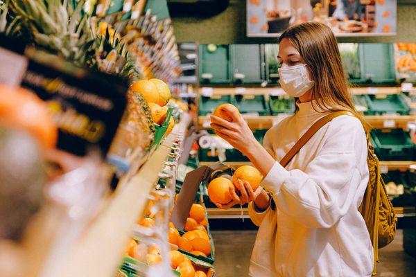 Mulher usa máscara em supermercado