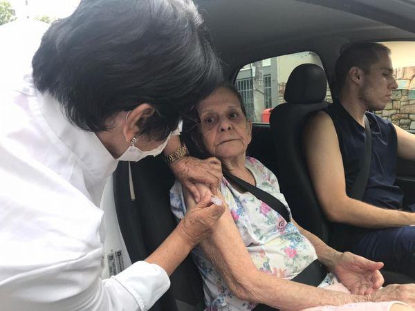 Profissional aplica vacina em idosa dentro do carro em Vitória
