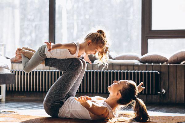Mãe brinca com a filha no tapete da sala