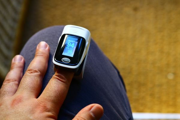 Pessoa com aparelho oxímetro no dedo para medir a saturação do oxigênio no sangue
