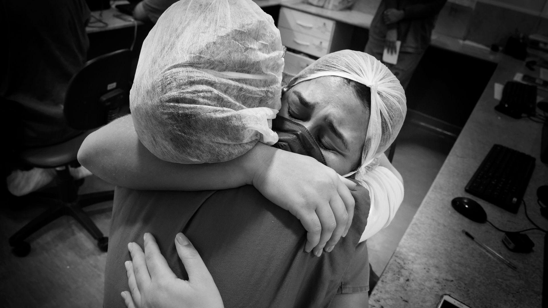 A enfermeira Laís de Castro chora abraçada à fisioterapeuta Larissa Giovannetti pela morte de paciente