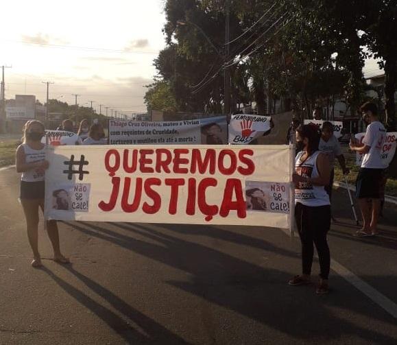 Pessoas na Rodovia Darly Santos, em Vila Velha, carregam faixas em protesto pela morte de Vívian Lima