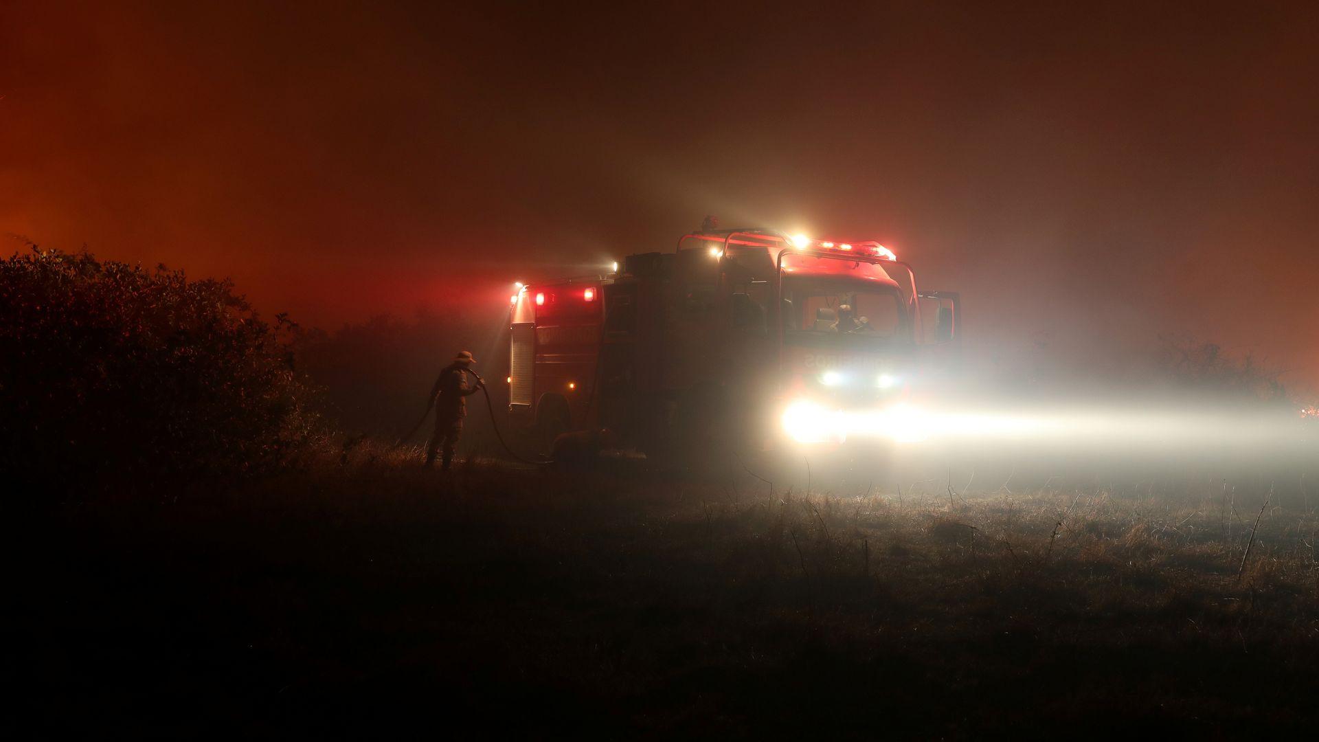 Bombeiro segura uma mangueira enquanto tenta apagar um incêndio em uma fazenda no Pantanal, a maior área úmida do mundo, em Pocone, Mato Grosso, Brasil, 26 de agosto de 2020. REUTERS / Amanda Perobelli PROCURE