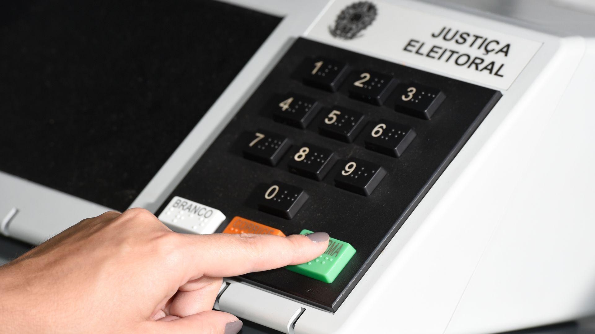 A urna eletrônica e o botão de confirma o voto