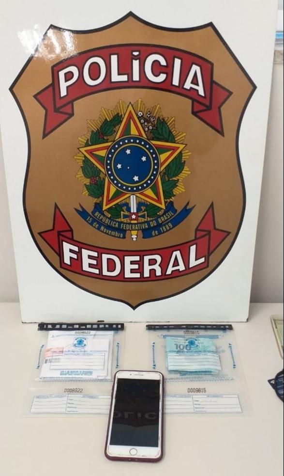 Notas falsas e um celular foram apreendidos pela Polícia Federal. Crédito: Polícia Federal | Divulgação