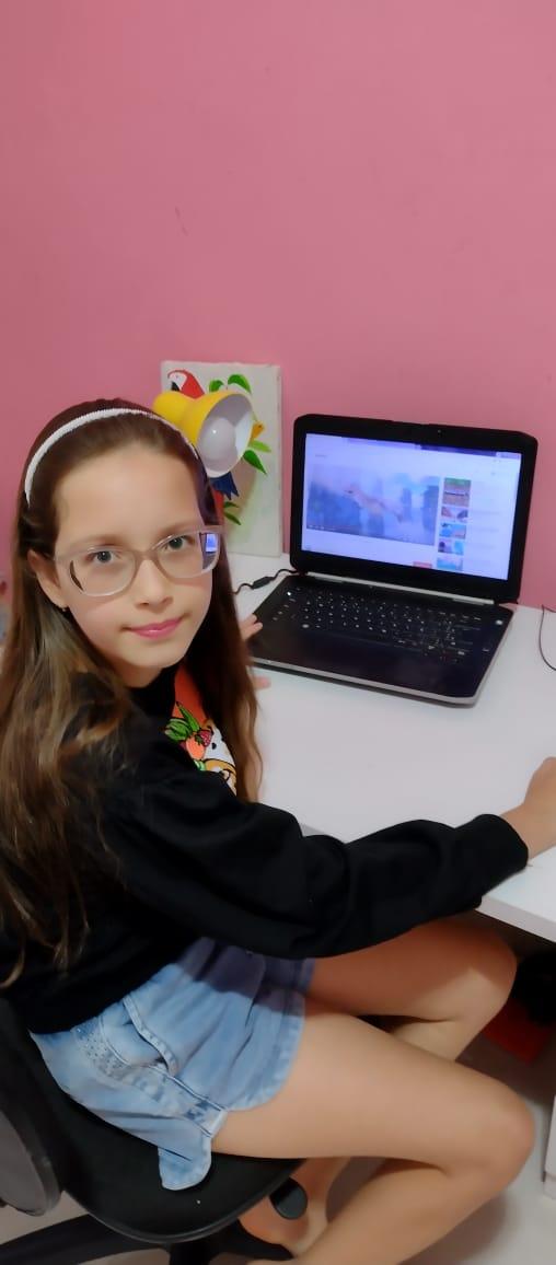 Mainy, de 10 anos, se senta diante do computador das 13h às 17h30 para participar das aulas on-line durante a pandemia.
