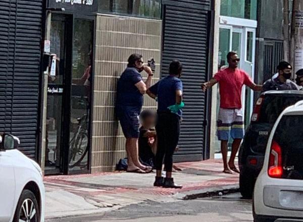 Criminoso aparece sentado no chão, cercado por pessoas; no canto direito é possível ver a presença dos policiais no local. Crédito: Telespectadora da TV Gazeta