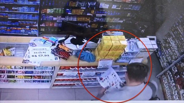 Homem aparece usando panfleto para esconder as mãos no momento em que furta aparelhos em farmácia